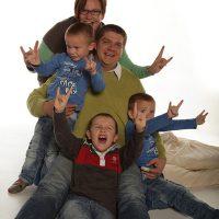 Familie mit drei Kindern zeigt die mano cornuta