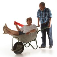 Alter Mann schiebt alte Frau in Schubkarre