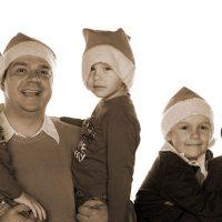 Familie mit drei Kindern mit Weihnachtsmützen