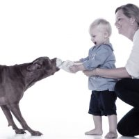 Mutter und Kind spielen mit Hund