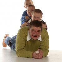 Liegender Mann mit drei Söhnen