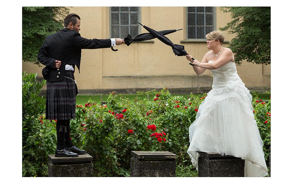 Brautpaar kämpft mit Regenschirm gegeneinander