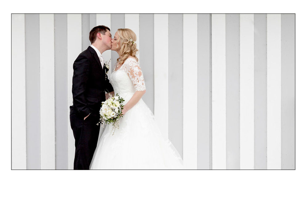 Brautpaar küßt sich vor heller Wand