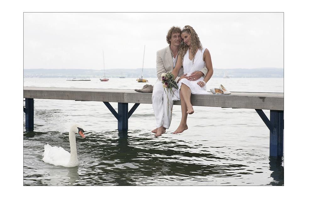 Brautpaar sitzt barfuß am Bodensee