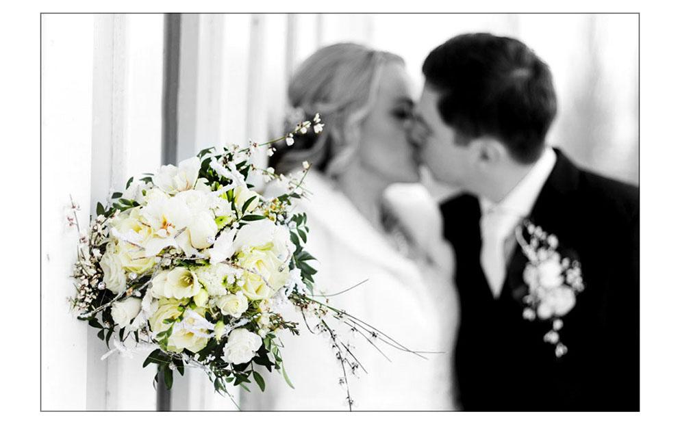 Brautstrauß im Hintergrund küßt sich ein Brautpaar