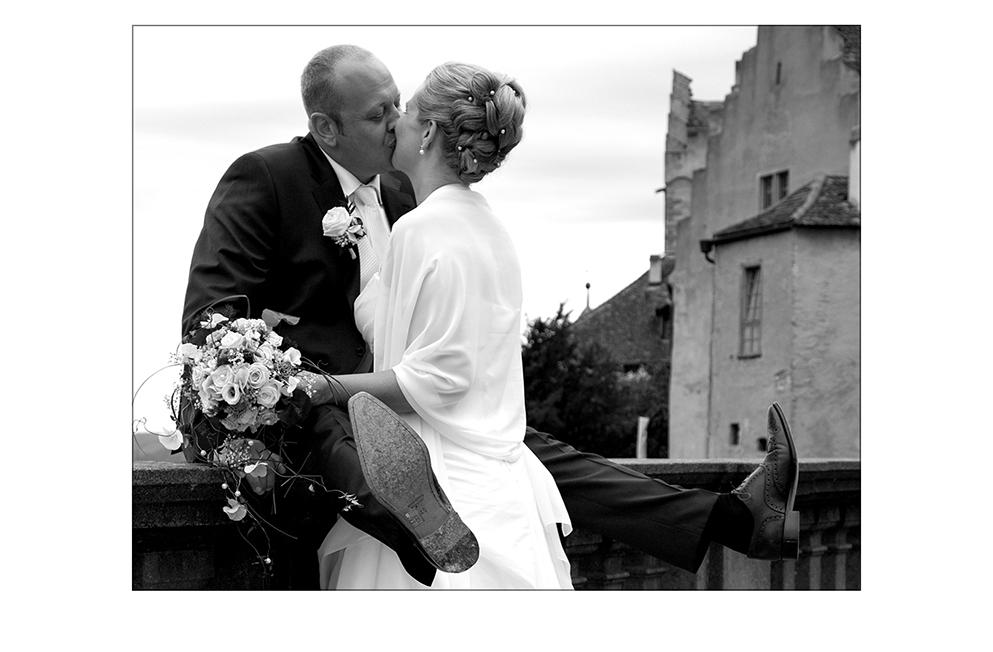 Braut küßt den auf der Mauer sitzenden Bräutigam