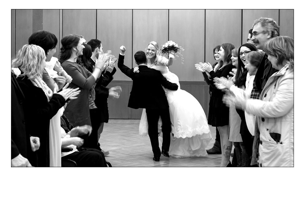 Bräutigam trägt Braut aus dem Standesamt